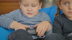 Cute girl and boy playing a game on the console Stock Footage