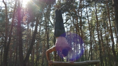 Strong muscular man doing a handstand in a forest. Athlete training outside Stock Footage