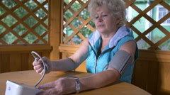 Woman measuring blood pressure with tonometer herself Stock Footage