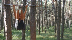 Athletic muscular man performing abdominal exercises on the horizontal bar Stock Footage