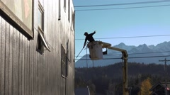 Man in Lift Boom Roller Painting Building Exterior Stock Footage