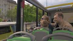 Family of three traveling in city by double-decker bus Stock Footage