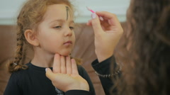 Woman draws the girl's face on Halloween party Stock Footage