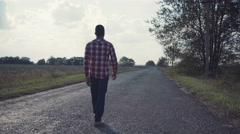 Stylish guy walking on road in rural Stock Footage