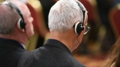 Unrecognizable person using in ear headphones for translation during event Stock Footage