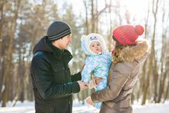 Parenthood, fashion, season and people concept - happy family with baby in Stock Photos