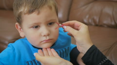 Drawing red color on the boy's face for Helloween Stock Footage