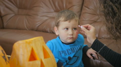 Painting red spiderweb on boy's face on Halloween Stock Footage