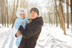 Happy father playing with little child son boy in winter park Stock Photos