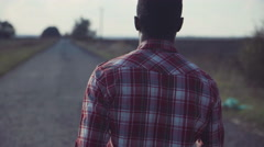 Black man going straight on countryside road Stock Footage