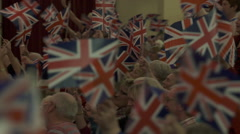 UNION JACK WAVING . British audience waving national flags panning shot. Stock Footage