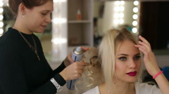 Hairdresser makes hairstyle blonde girl Stock Footage