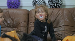 Girl ith false teeth try to scary on Halloween Stock Footage
