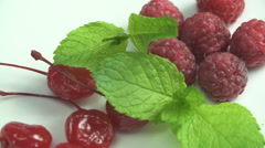 Closeup berries on a plate of to decorate cakes. Raspberry, cherry and mint Stock Footage