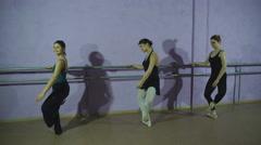 Three ballerinas Practicing At Ballet Barre In Dance Studio Stock Footage