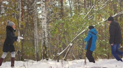 Family playing by throwing snowballs in the winter Park Stock Footage