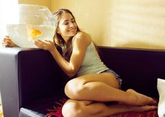 Pretty woman playing with goldfish at home Kuvituskuvat