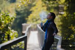 Young man with custom box mode vape device vaping an electronic cigarette Stock Photos