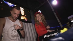 Happy dj girl in red dress with rim on head at turntable in nightclub. Mc man Stock Footage