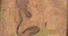 An aerial vertical shot of a valley with a stream flowing through it Stock Footage