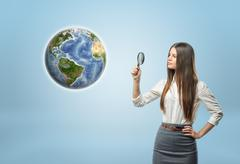 Full portrait of businesswoman looking at Globe Earth through a magnifier Stock Photos