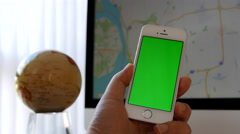 Close up hand holding green screen iphone and using google map on iMac Stock Footage