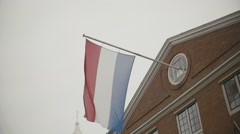 Flag of Netherlands flying on building in Amsterdam, Holland, slow-motion Stock Footage