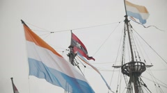 Flag of Netherlands and the symbol of Amsterdam - triple x flying on building in Stock Footage