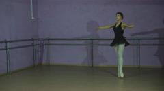 Beautiful graceful ballerine in black practice arabesque ballet position in hall Stock Footage