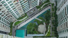Aerial timelapse of people in decorative garden outside apartment blocks Stock Footage