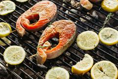 Grilled salmon steak on the flaming. Side view Stock Photos