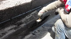 The roofer applies bituminous mastic on a roof Stock Footage