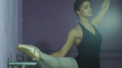 Ballerina stretches herself near barre and wall in the classroom Stock Footage