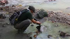 Machete sharpening in the stream, Borneo Stock Footage