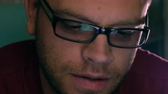 Serious handsome young man in black rim glasses using his tablet computer and Stock Footage