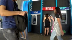 People passing across a lady withdrawing ATM Stock Footage