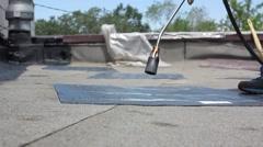 Roofers repair bitumen roof using a gas burner Stock Footage