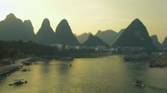 Yangshuo city with boats and karst hills reflecting in calm waters of Li river. Stock Footage