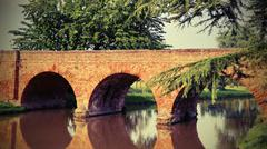 Medieval bridge made of red brick with arches Stock Photos