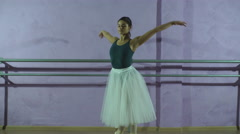 Wearing pointe shoes ballerina dances near barre in dancing hall Stock Footage