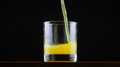 Pouring orange juice soda in glass in slow motion Stock Footage