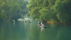 The bamboo raft with visitors goes on the Yulong river in Yangshuo Stock Footage
