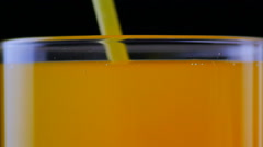 Close up of drinking orange soda with a straw at black background Stock Footage