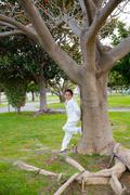 Young First Communion boy leaning on a big tree Stock Photos