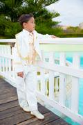 Young First Communion boy leaning on a white wooden fence over a bridge Stock Photos