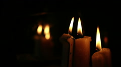 Paraffin candles are lit in the darkness in front of a mirror. Stock Footage