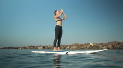 Woman exercising yoga on a surf board Stock Footage
