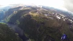 Skydiver open parachute above mountains covered by greenery. Extreme sport Stock Footage