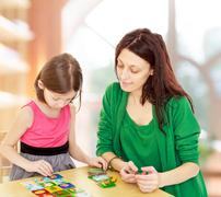 Mom and daughter at the table playing educational games Kuvituskuvat