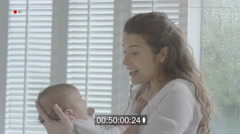 4K Portrait of new mother holding baby daughter at home & being filmed on video Stock Footage